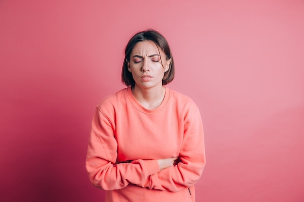Woman wearing casual sweater on background suffering stomach ache with painful grimace, feeling sudden period cramps, gynecology concept