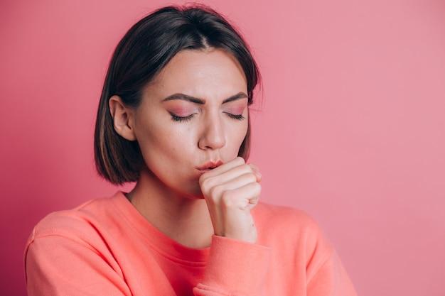 감기 나 기관지염의 증상으로 몸이 좋지 않고 기침을하는 배경에 캐주얼 스웨터를 입은 여성. 건강 관리 개념.