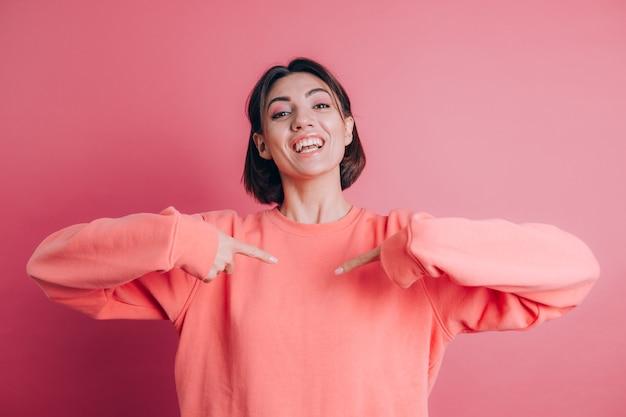 긍정적이고 쾌활한 미소, 손가락으로 자신을 가리키는 배경에 캐주얼 스웨터를 입고 여자