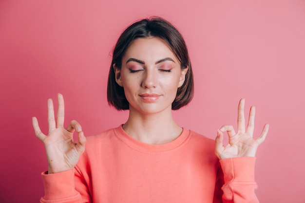 Женщина, носящая повседневный свитер на фоне, расслабляется и улыбается с закрытыми глазами, делая жест медитации пальцами. концепция йоги.