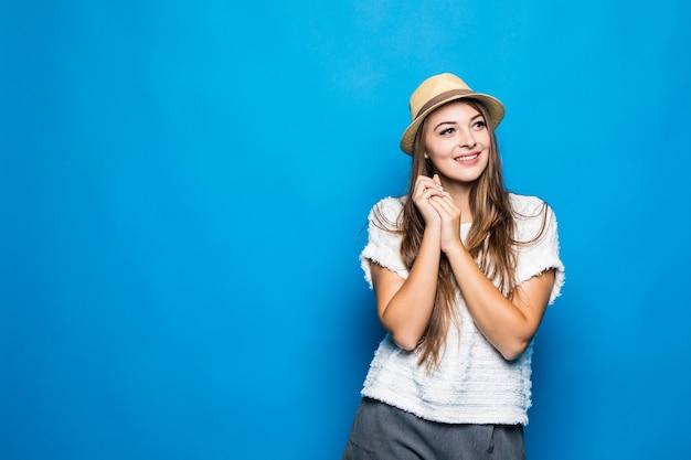Женщина в повседневной белой рубашке и шляпе на синем
