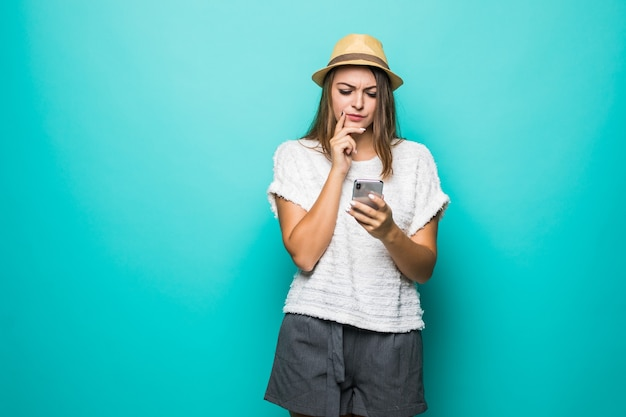 Женщина в повседневной белой рубашке и шляпе с помощью смартфона на синем