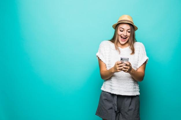 青のスマートフォンを使用してカジュアルな白いシャツと帽子を着ている女性