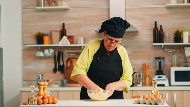 Woman wearing chef bonete while mixing cracked eggs with flour in kitchen while preparing food following traditional recipe. retired elderly baker kneading in glass bowl ingredients for homemade cake
