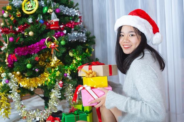Женщина в рождественской шапке счастлива с рождественским подарком