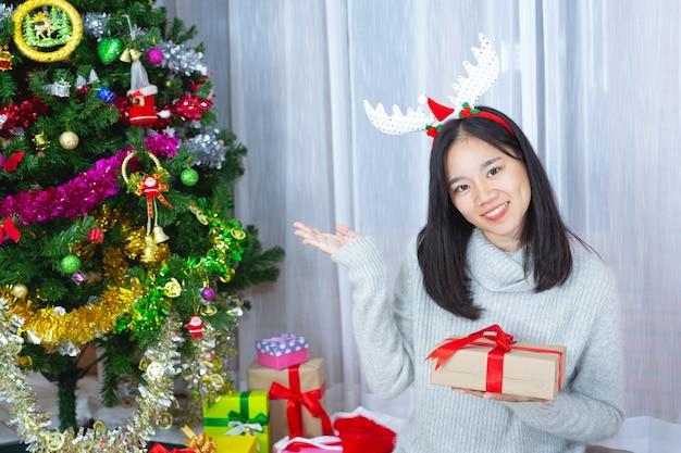 Donna che indossa il cappello di natale felice con un regalo di natale