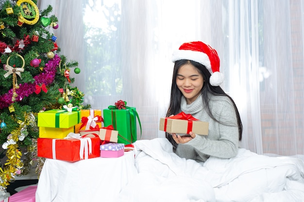 Woman wearing christmas hat happy with christmas present