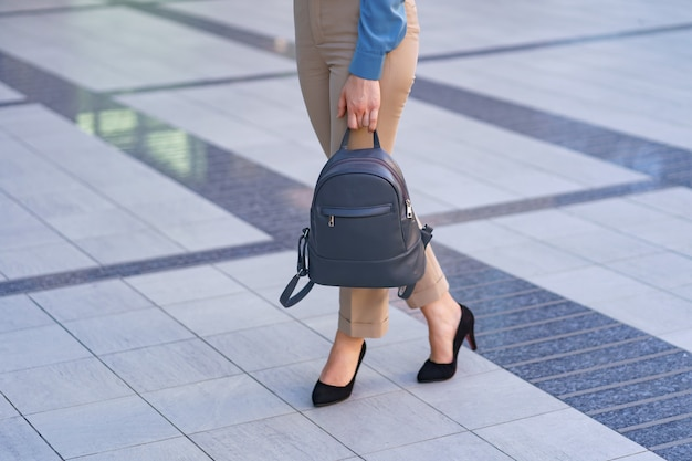 Woman wearing classic black high heel toe shoes while posing with a gray leather backpack. model posing on the street. elegant outfit. close up.