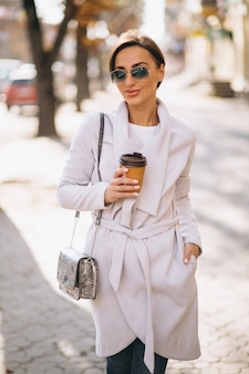 Woman wearing coat and drinking coffee