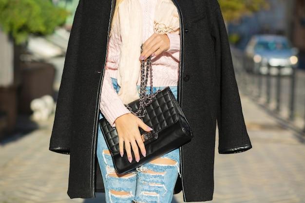 黒革の財布を保持しているコート、ジーンズ、セーターを着ている女性。クローズアップショット