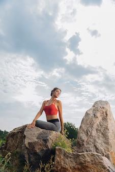 Женщина в удобной спортивной одежде, наслаждаясь свежим воздухом, растягиваясь возле скал