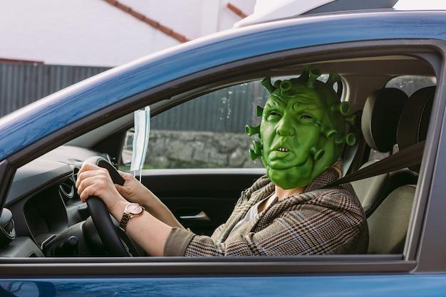 衣装を着た女性-covid-19コロナウイルスマスクが車を運転し、窓から覗く