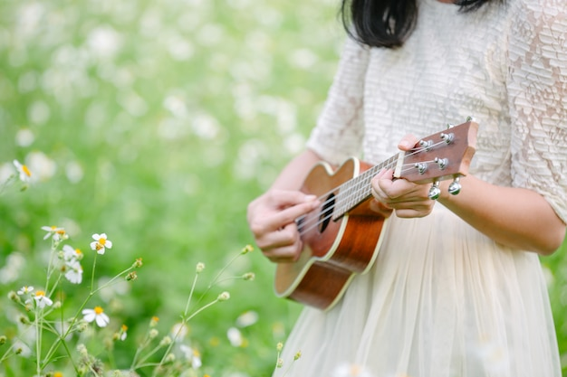 Woman wearing a cute white dress and playing ukulele