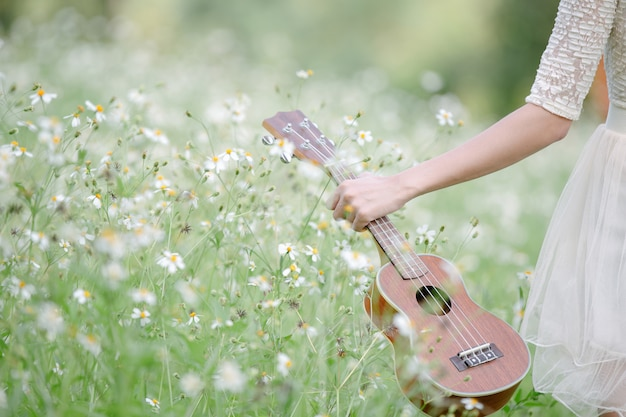 Woman wearing a cute white dress with an ukelele
