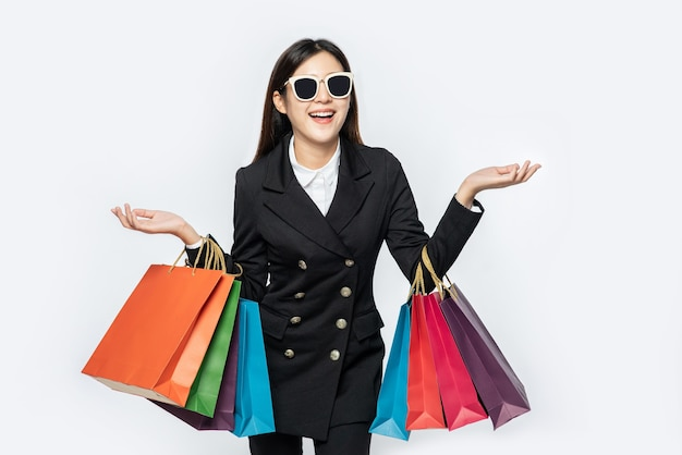 The woman wearing dark clothes and glasses, along with many bags, to go shopping