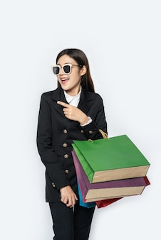 La donna indossa abiti e occhiali scuri, insieme a tante borse, per fare la spesa
