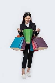 La donna indossa abiti scuri, insieme a tante borse, per fare la spesa