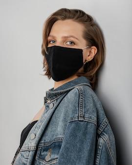 데님 재킷과 마스크를 착용하는 여자