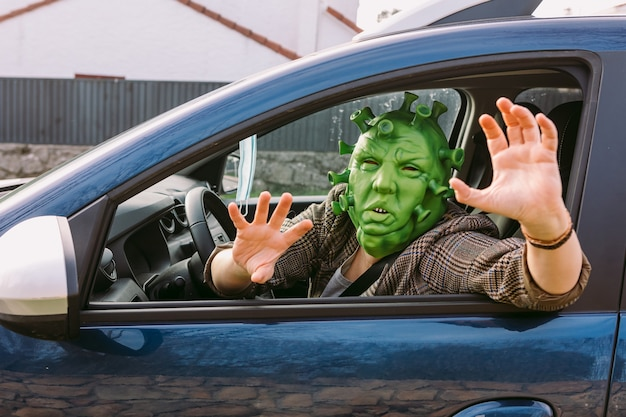 Woman wearing disguise - coronavirus covid-19 mask driving a car, peeking out the window, scaring