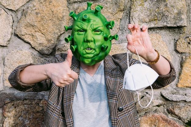 変装した女性-ffp2マスクを保持し、ok指を上げるcovid-19コロナウイルスマスク