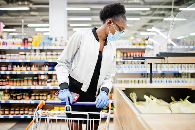 일회용 의료 마스크와 장갑 코로나 바이러스 pandemia 발발 동안 슈퍼마켓에서 쇼핑하는 여자.