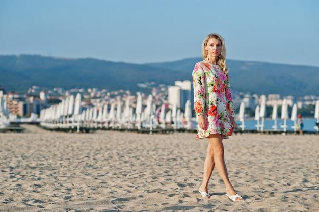 海の砂浜に立っているドレスを着ている女性