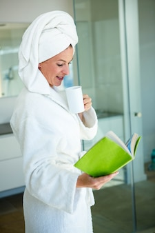 Woman wearing a dressing gown, reading a book and drinking a cup of coffee
