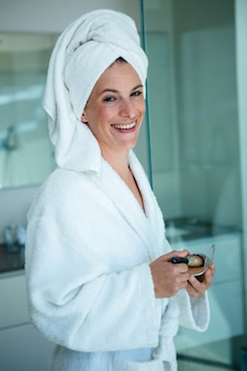 Woman wearing a dressing gown and a towel on her head is holding face powder and a make up brush
