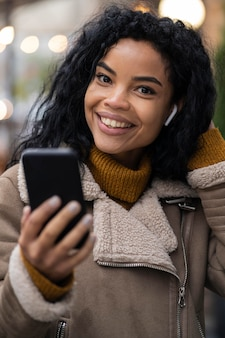 屋外で音楽を聴くためにイヤフォンを身に着けている女性