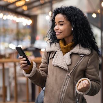 外で音楽を聴くためにイヤフォンを身に着けている女性