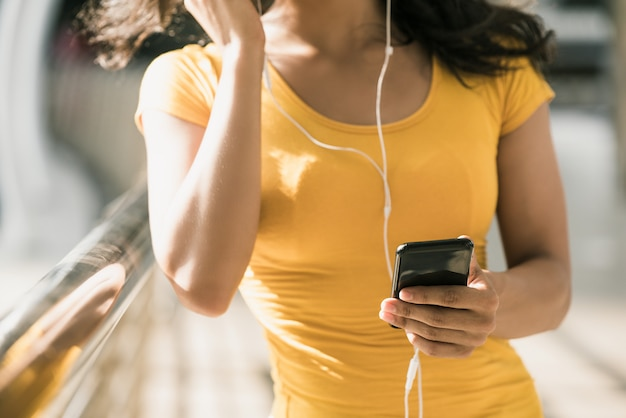 Woman wearing earphones listening to music from smartphone