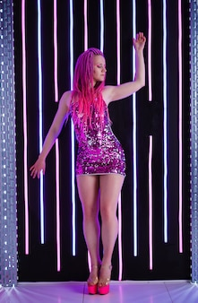 Woman wearing elegant black sequin strap cami dress standing on dark interior with neon light. attractive caucasian female model posing against glowing neon lamps on background