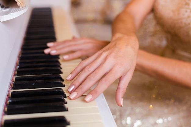 집에서 피아노 연주 저녁 빛나는 황금 크리스마스 드레스를 입고 여자.