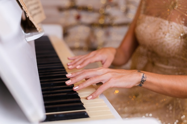 Женщина, носящая вечернее блестящее золотое рождественское платье, играет на пианино у себя дома.