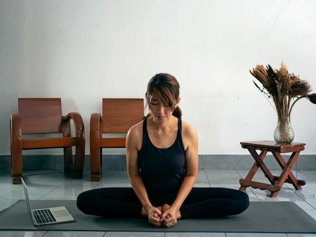 Woman wearing exercise suit,sitting on yoga mat,stretching body by learning from laptop,doing activity at home.