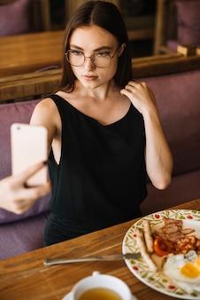 Woman wearing eyeglasses taking selfie from mobile phone in the restaurant