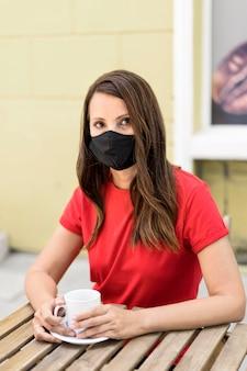 Donna che indossa la maschera in tessuto e che tiene una tazza di caffè vista frontale