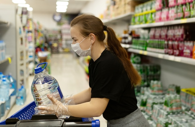 Женщина носить маску и перчатки, покупая в супермаркете, улыбаясь, держа бутылку воды. панические покупки во время пандемии коронавируса covid-19. бюджетные покупки в магазине товаров.