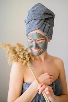 フェイスマスクを着て、花とポーズの女性