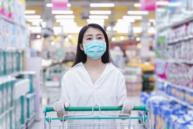 Лицевая маска женщины нося и резиновая перчатка нажимают магазинную тележкау в универмаге suppermarket.