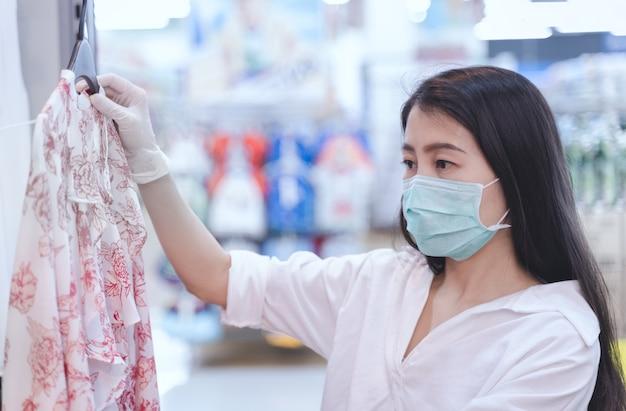 Женщина носить маски и резиновые перчатки покупки в супермаркете.