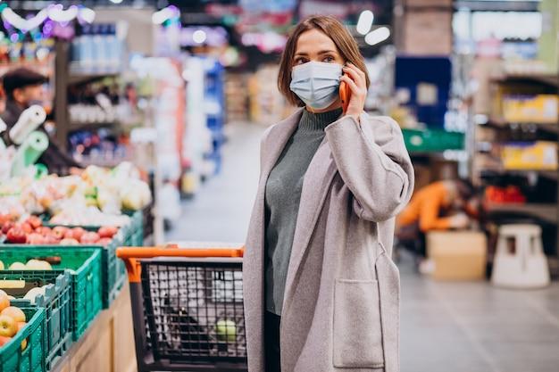 フェイスマスクを着用し、食料品店で買い物をする女性