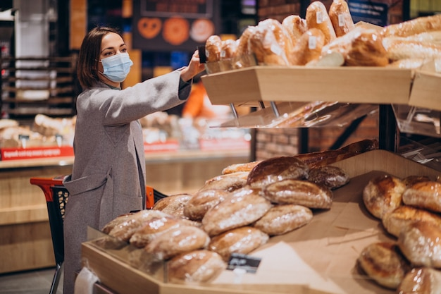 Женщина в маске для лица и покупки в продуктовом магазине