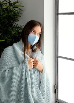 집에서 얼굴 마스크를 착용하는 여자