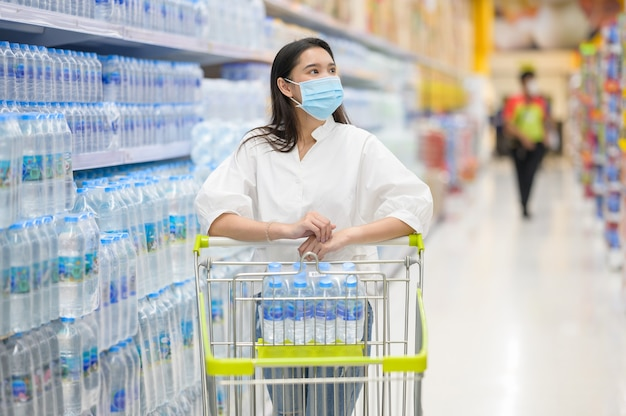 슈퍼마켓에서 구매하는 얼굴 마스크를 착용하는 여자
