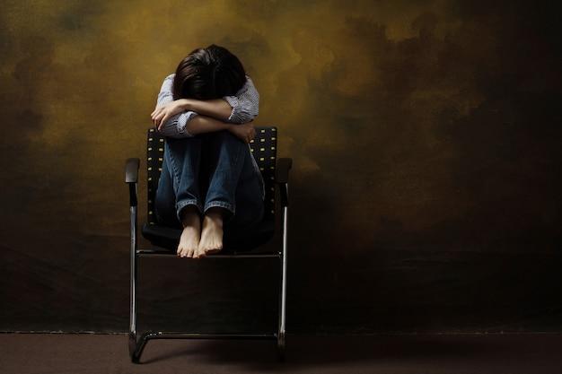 Женщина в маске от депрессии почесывает голову, сидя на стуле. депрессия, связанная с covid-19