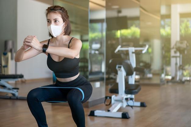フィットネスセンターでストラップを伸ばして戦利品機器でスクワットを行うフェイスマスクを着ている女性。コロナウイルスのパンデミック中。