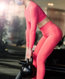 코로나 바이러스 전염병 동안 체육관에서 얼굴 마스크 운동을 하는 여성.
