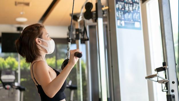 체육관에서 위도 풀다운 케이블 기계에 운동 및 근육 flexing 얼굴 마스크를 착용하는 여자. 코로나 바이러스가 유행하는 동안.
