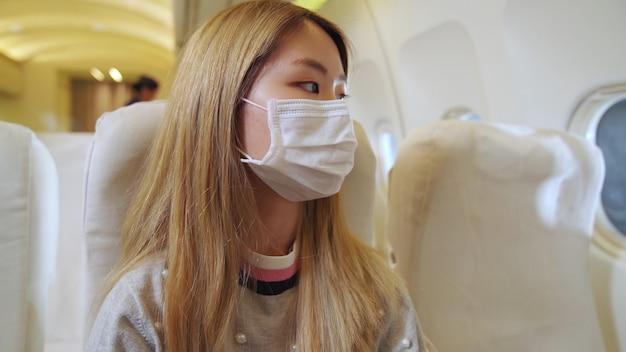 飛行機の中でフェイスマスクを着用している女性